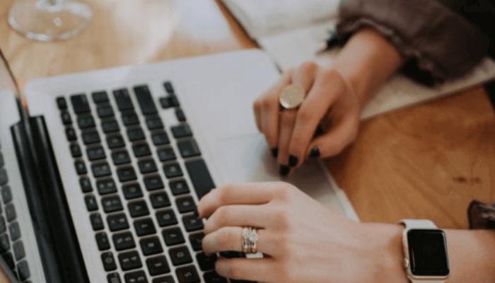 A lady typing a laptop